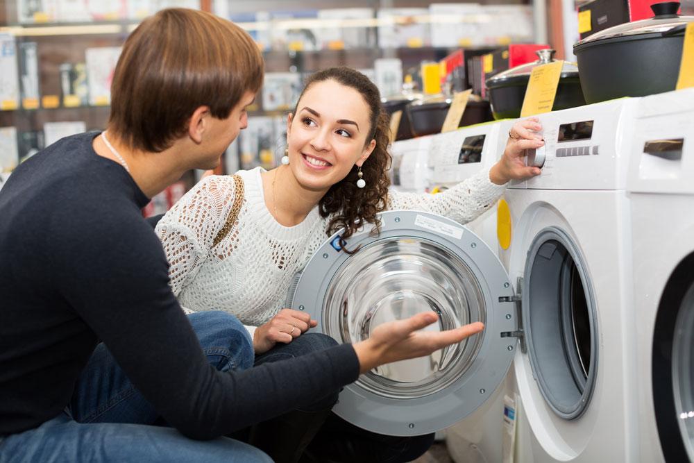 Junges Paar kauft neue Waschmaschine